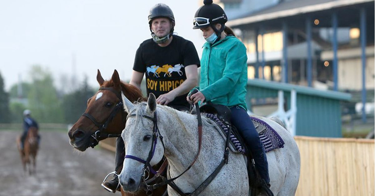 JOE HUMBER gallops and work his big stable of horses at Fort Erie racetrack. Here he is on o one of his runners while Nicole Collee accompanies on the pony. LAURIE LANGLEY PHOTO